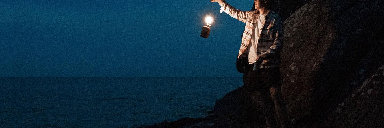 Trovare La Felicità, Immagine Di Uomo Con Lanterna Ai Bordi Del Mare.